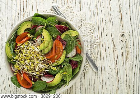 Healthy Green Salad With Alfalfa Sprouts, Avocado And Fruit On Wooden Background