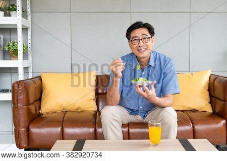 Senior Asian Men Sitting On The Sofa At Home While Eating Green Vegetable Salad And Organic Orange J