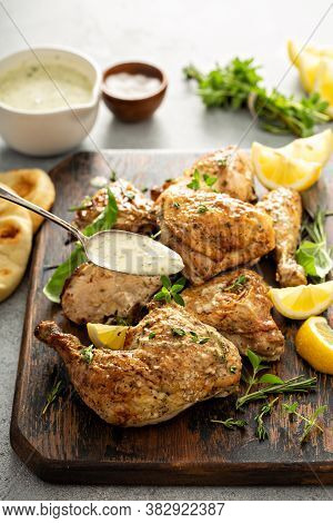 Lemon Herbed Garlic Roasted Chicken Carved Into Pieces On A Wooden Board