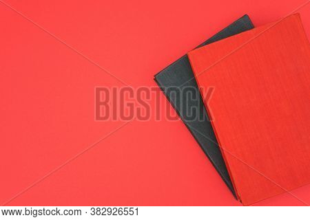 Red And Black Books On A Red Background. Copy Space