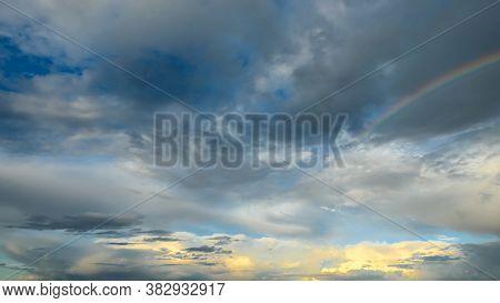 Amazing Dramatic Sky. Cloudy Weather Turning Rainy. Cumulonimbus In Atmosphere With Rainbow.
