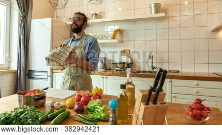 Young Man, Italian Cook Wiping His Hands With Kitchen Towel After Cutting Vegetables While Preparing