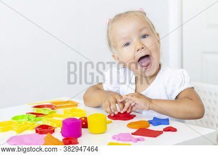 Toddler Sculpts From Colored Plasticine On A White Table. The Hand Of A Small Child Squeezes Pieces
