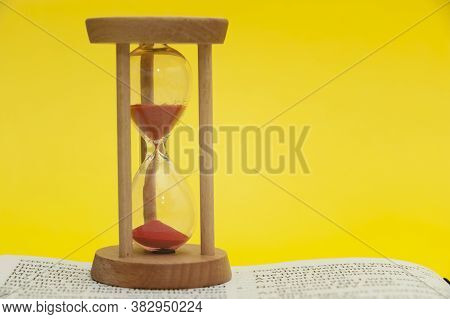 Red Sand Hourglass On Top Of Open Holy Bible In The Book Of The Prophet Ezekiel Chapter 7 Verse 7. I