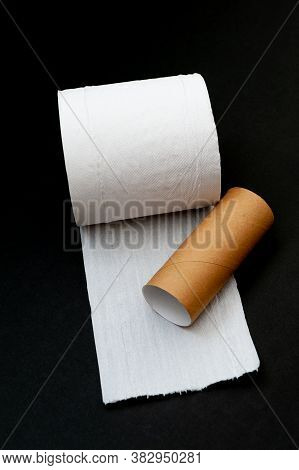 Single Roll Of Unrolled White Toilet Paper And Paper Core Tube. Isolated On Black Background. Close-