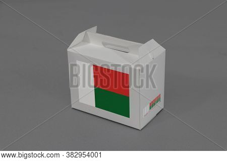 Madagascar Flag On White Box With Barcode And The Color Of Nation Flag On Grey Background. The Conce