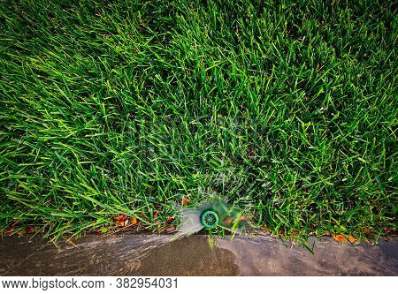 Water Sprinkler Mounted Against A Parapet And Watering The Grass In The Backyard View From Above
