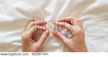Close Up. A Young Girl Holds A Condom In A Hand In A White Bed. The Concept Of Sex And Eroticism.
