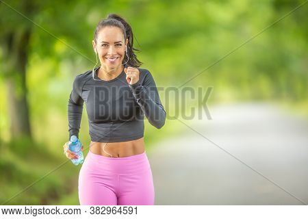 Young Woman Runner Running With A Bottle Of Water.