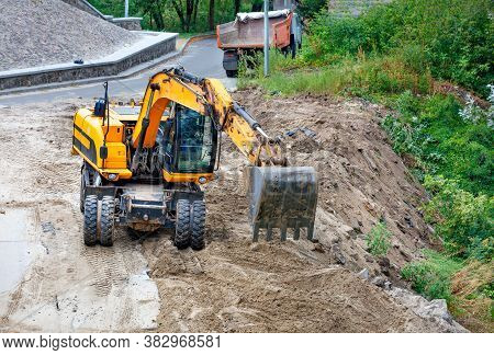 A Heavy Construction Excavator With Its Bucket Levels The Sand And Backfills The Ravine To Widen And