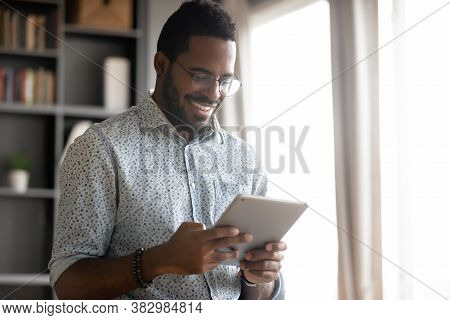 Smiling African American Man Holding Computer Tablet, Looking At Screen