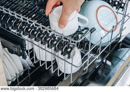 Dishwasher Machine. Woman Hand Taking Out Clean Dish After Washing.