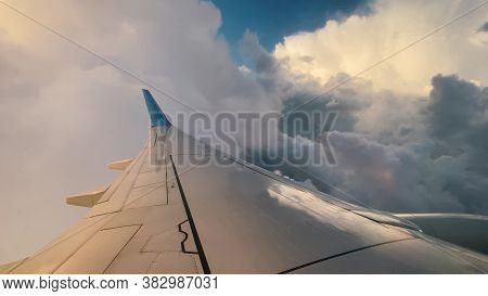 Long White And Blue Wing Of Modern Airplane Flying In Fluffy White Clouds In Stratosphere On Nice Su