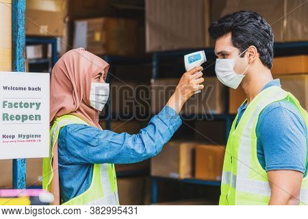 Muslim Woman Worker Uses Medical Digital Infrared Thermometer Measure Temperature To Indian Man Work