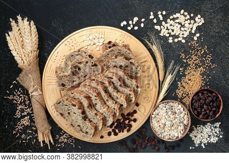 High fibre health food with raisin rye bread loaf, bowls of raisins and muesli, with barley flakes, flax seed and sheaths of grain. High in antioxidants, omega 3, vitamins and protein with low gi.