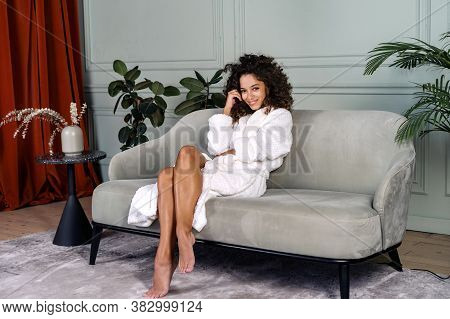 Concept Of Natural Beauty. Full Length View Of Happy Young Afro American Woman In Bathrobe Sitting A