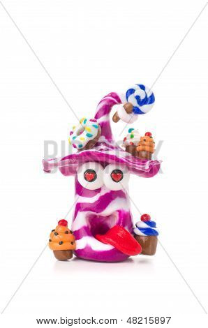 Handmade modeling clay figure with sweets on a white background