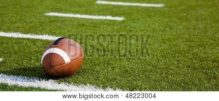 Ein American Football auf einem grünen Fußballplatz