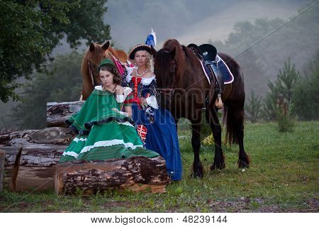 Two women in the royal baroque dress sitting next to the horses in the fog poster