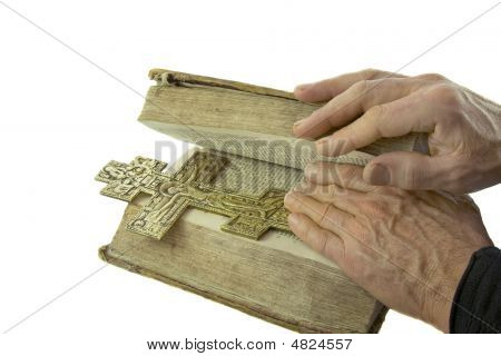 Male Hand Closed The Vintage Bible With Cross On It Isolated Over White Background