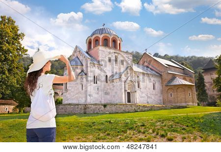 Beautiful young woman with white hat in front of Monastery Studenica, Serbia. poster