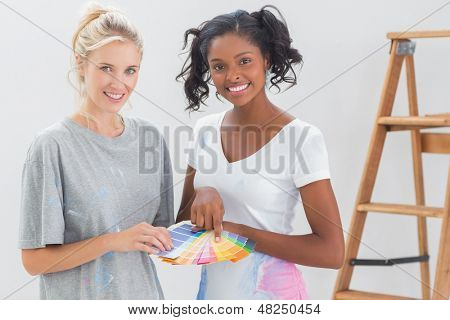 Young housemates choosing color for wall and looking at camera in new home
