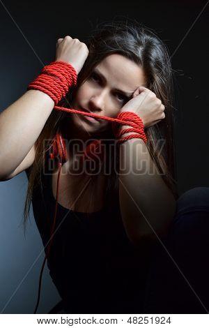 schöne junge Frau mit dem roten Seil gebunden