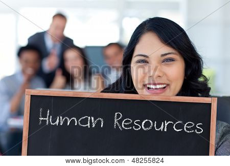 Businesswoman holding a blackboard with human resources written on it