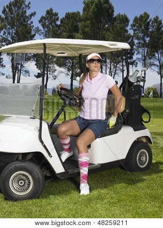 Beautiful female golfer wearing sunglasses disembarking from golf cart