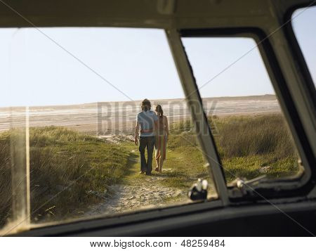 Full length of loving young couple walking towards beach view from campervan window