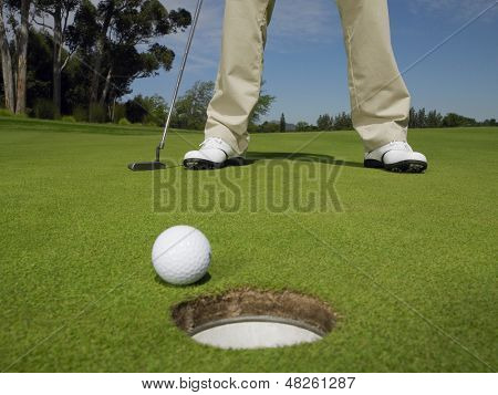 Low section of male golfer on green with ball at hole in foreground