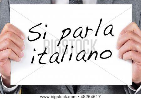 a man wearing a suit holding a signboard with the sentence si parla italiano, we speak italian, written in italian, in it