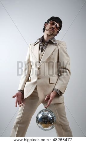 Low angle portrait of a retro man in a 1970s leisure suit and sunglasses holding a disco ball - mirror ball between his legs poster