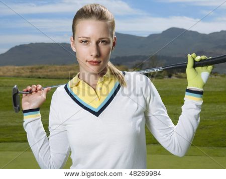 Portrait of beautiful female golfer with club on golf course