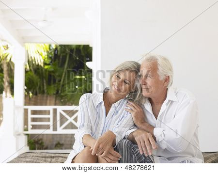 Happy middle aged couple sitting on verandah poster