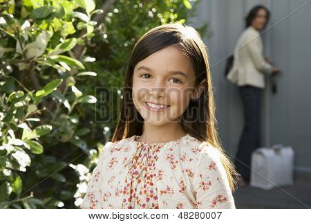 Portrait of young girl smiling in frontyard with mother locking house door