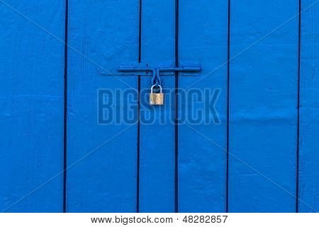 Old Brass Padlock On Wooden Blue Gate