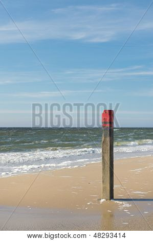 Wooden red beach pole at the coast of the Northsea