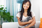 Young happy woman sitting on sofa with her cat at home poster