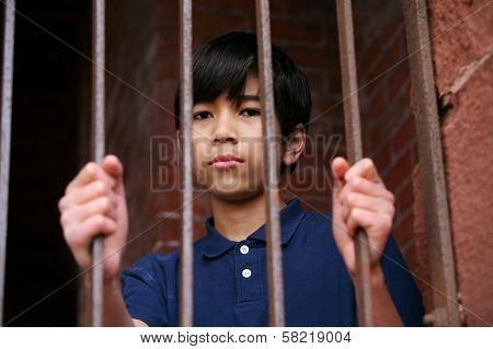 Boy Standing Behind Bars