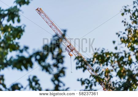 Hoisting Crane View Through Trees Leaves