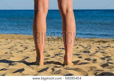 Legs Of Young Sunburnt Woman. Standing On Seashore.