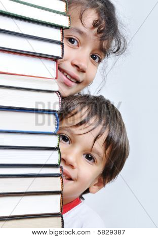 A Big Tower Of Many Books Vertical And Kids Hiding Behind