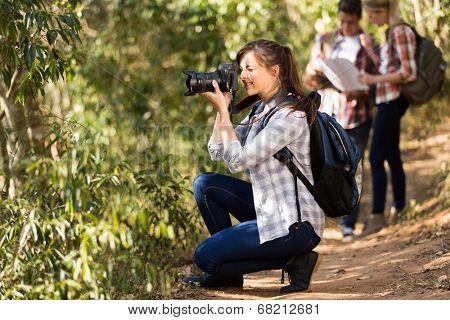 beautiful woman taking photos during hiking trip