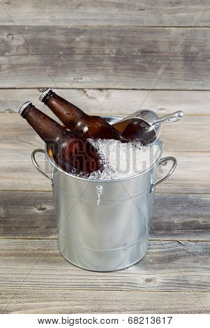 Vertical view of two unopened bottles of beer sitting inside metal bucket filled with crushed iced and rustic wood in background poster