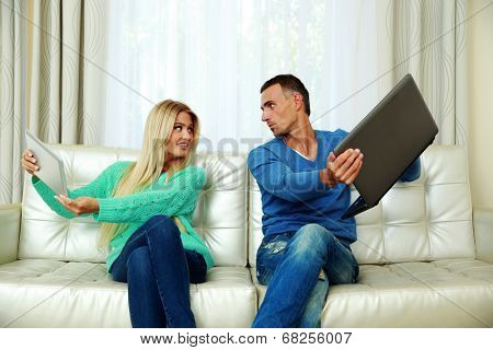 Funny couple sitting on the sofa with laptop and tablet computer at home