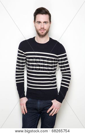 Portrait of an attractive young man in striped sweater posing against white background poster