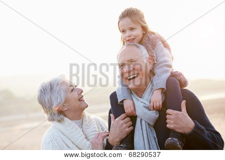 Grandparents And Granddaughter Walking On Winter Beach