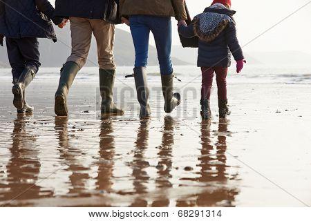 Close Up Of Family Walking Along Winter Beach