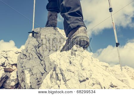 Close up of hiking shoes and trekking poles ascending a mountain poster